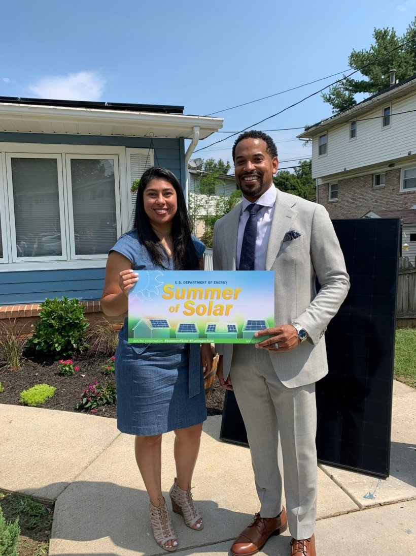 """Two people standing in front of a home with solar panels holding a sign that says """"Summer of Solar"""""""