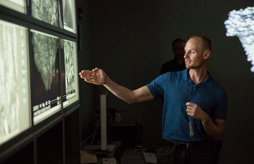 Photo of a man pointing to images of catalytic fast pyrosis