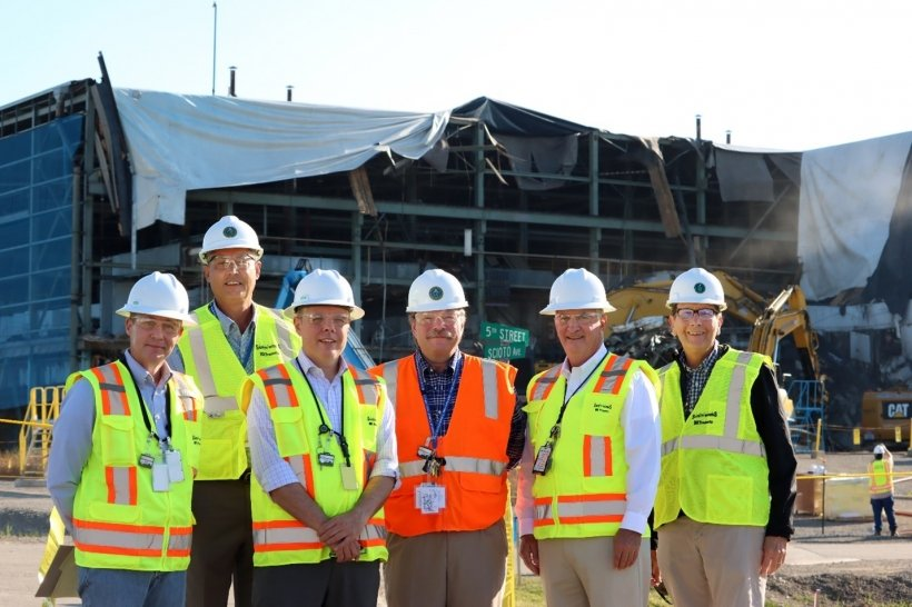"""From left, EM Acting Chief of Staff Erik Olds, Portsmouth/Paducah Project Office (PPPO) Deputy Manager Joel Bradburne, EM Acting Assistant Secretary William """"Ike"""" White, PPPO Manager Robert Edwards, DOE Associate Under Secretary for Environment, Health, Safety and Security Matthew Moury, and Portsmouth Site Lead Jeff Bettinger stand in front of the X-326 Process Building under demolition."""