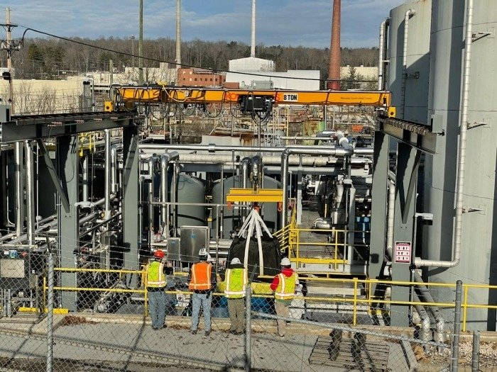 Workers observe the installation of the final components of a new zeolite treatment system designed to strip contaminants from wastewater at Oak Ridge.
