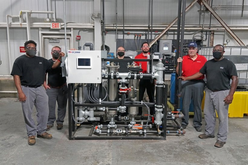 several people standing in a manufacturing facility