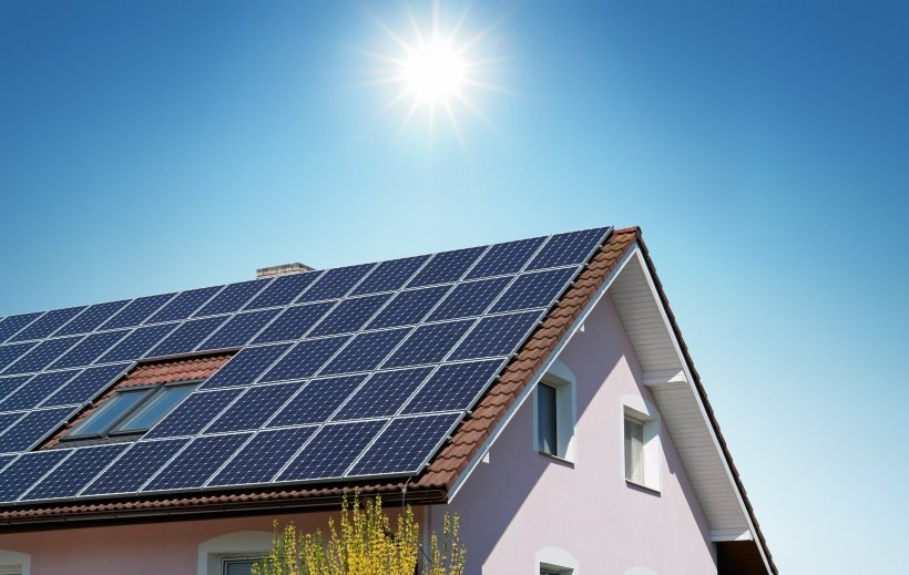 A house with rooftop solar panels and the sun shining above it.