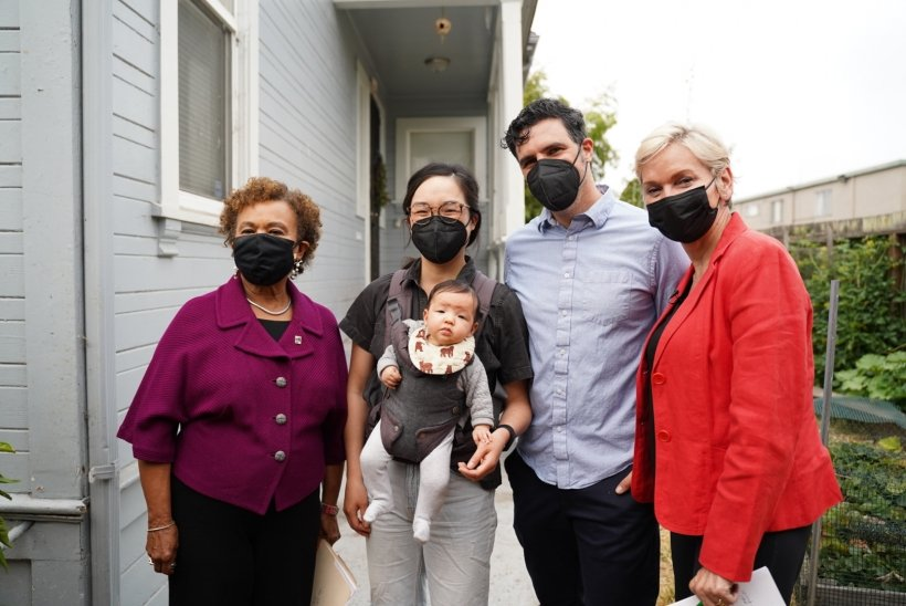 A group of people posing together and wearing masks.