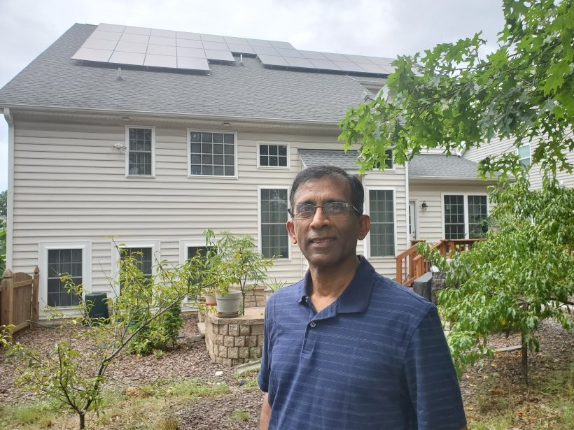 A person standing in front of a house with solar panels on the roof