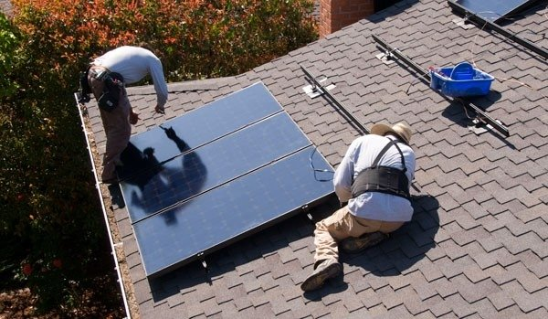 Two installers secure solar photovoltaic panels on a residential roof.