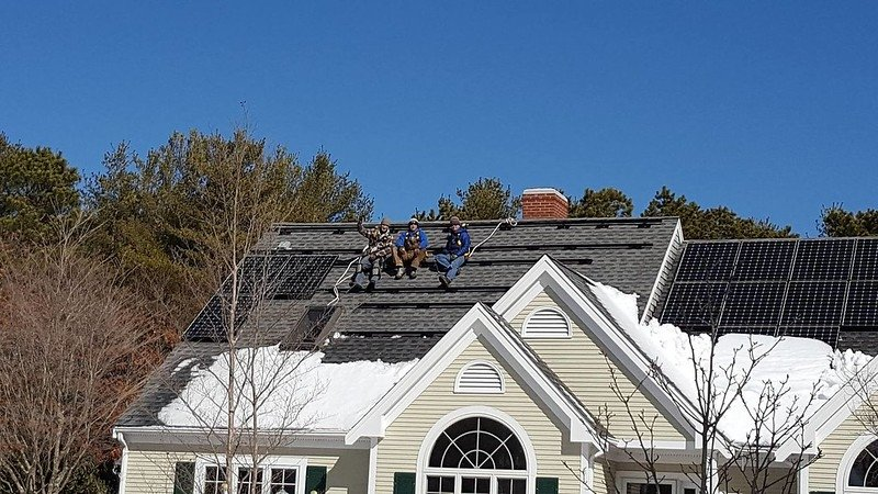 solar workers on top of a residential home.