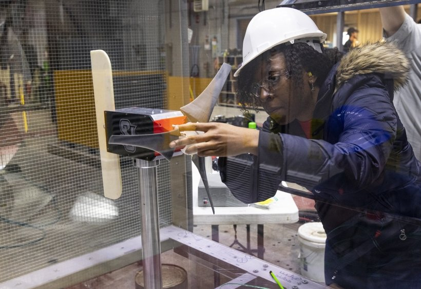 A young woman in a hard hat and safety glasses adjusts a small wind turbine in a laboratory setting.