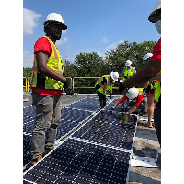 Team members work together to install solar panels in the community solar array on the rooftop of Crescent Park Village.