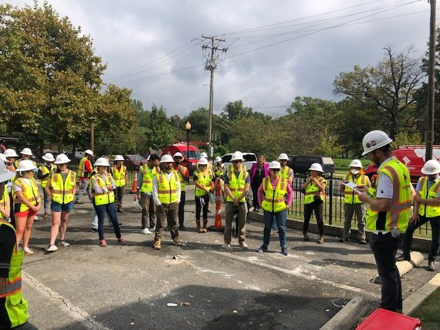 Team members, wearing hard hats and safety vests, receive a briefing from their crew leader before beginning a community solar installation in Washington, DC.