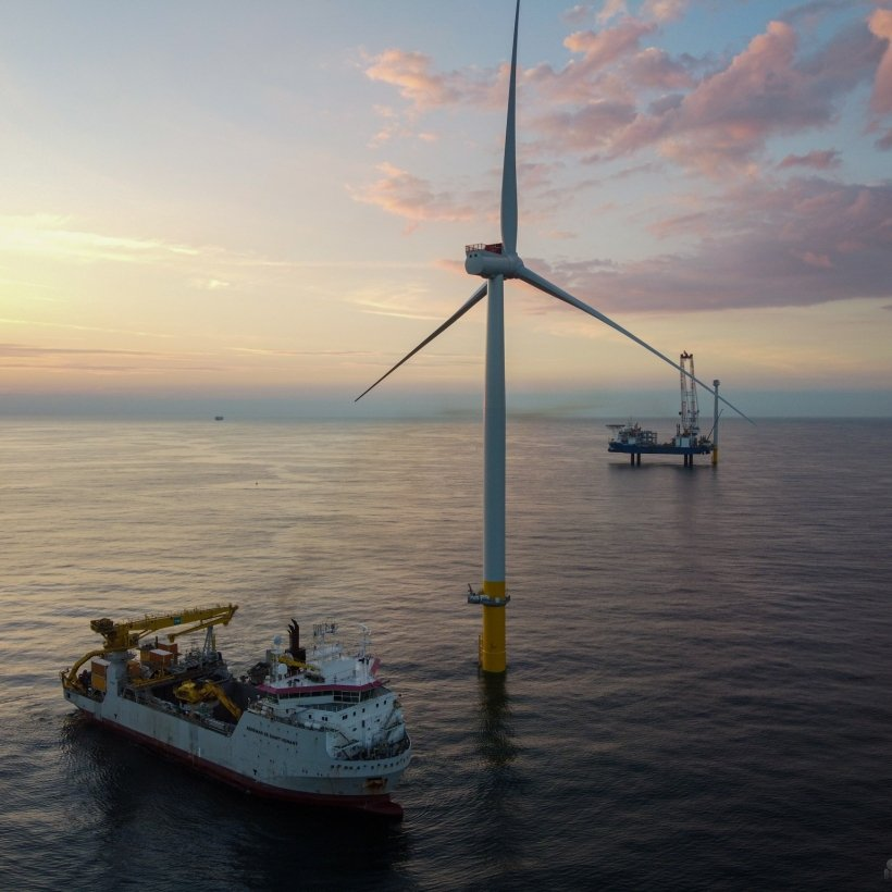 Offshore wind turbine and a boat at sea.