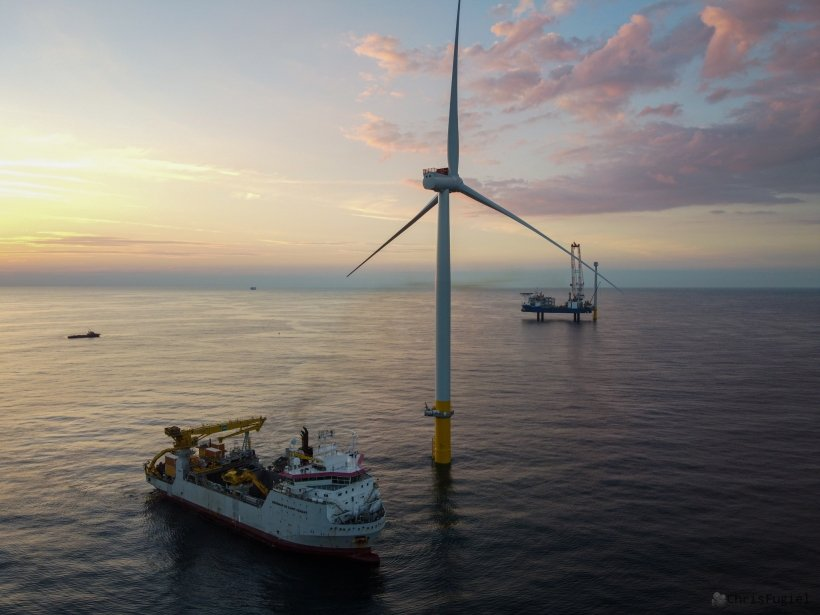 An offshore wind turbine in a calm ocean with a service vessel nearby; a platform is in the distance, erecting another wind turbine. The sun is rising (or setting) in the distance behind light clouds.