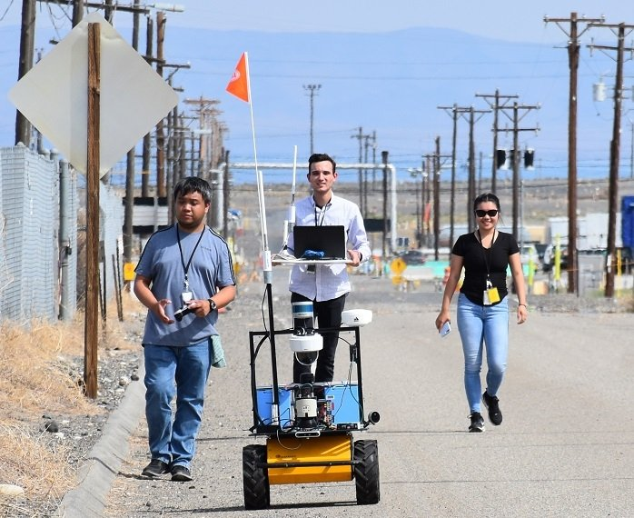 During a recent road closure on the Hanford Site, Florida International University students, from left, Jeff Natividad, Joel Adams, and Thi Tran, test a radiation mapping robot outside a tank farm. The students are part of a unique internship program between EM and the university.