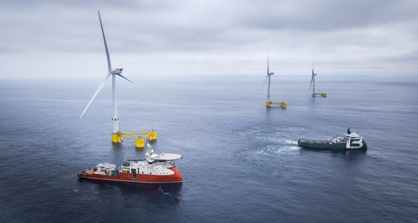 Photo of three offshore wind turbines with two ships in the foreground.