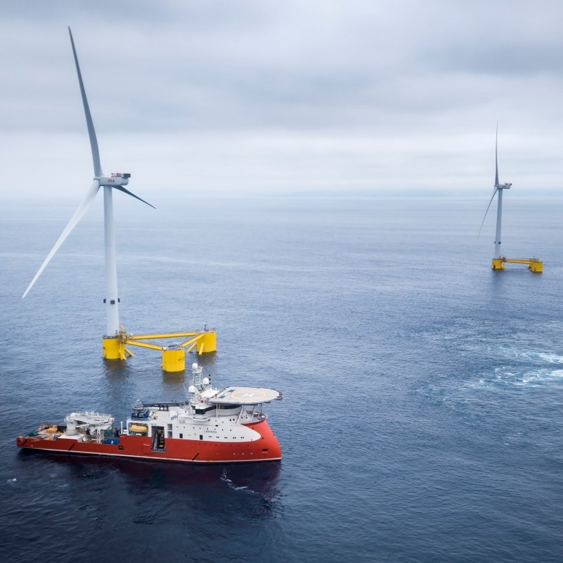 Offshore wind turbines and a boat at sea.
