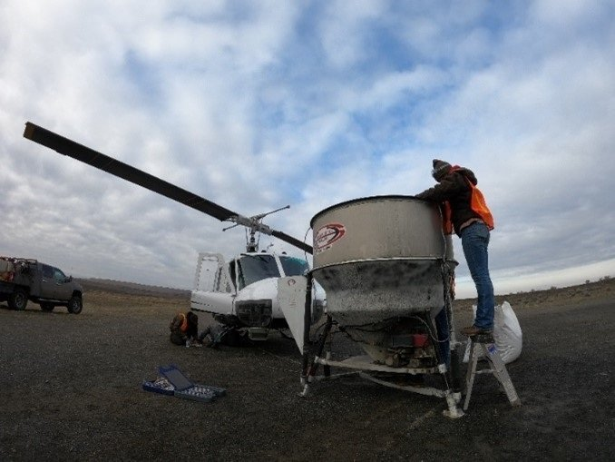 Workers ready a hanging bucket for a helicopter used to drop native grass and shrub seed on the Hanford Site after a fire destroyed 5,500 acres of critical habitat in June 2020.
