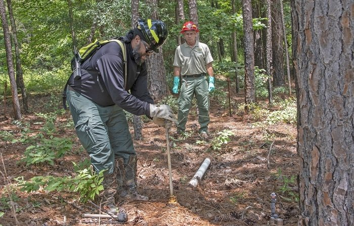 At EM's Savannah River Site, U.S. Forest Service employees Secunda Hughes, left, a civil engineering technician, and Andrew Thompson, a forester, inspect irrigation piping and sprinkler heads, part of a 62-acre pine plantation used to safely disperse tritium into the atmosphere and away from local waterways.