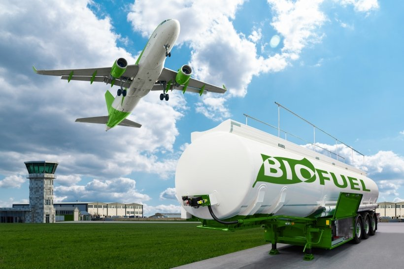An airplane flying, with a trailer of biofuel in the foreground.