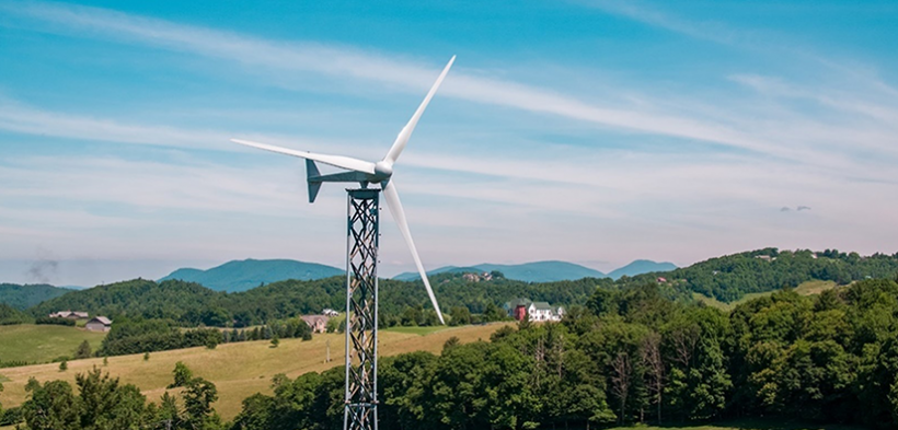Distributed wind turbine with mountains in the background.