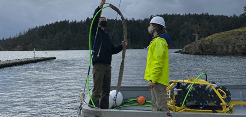 Two men on a boat setting up equipment.