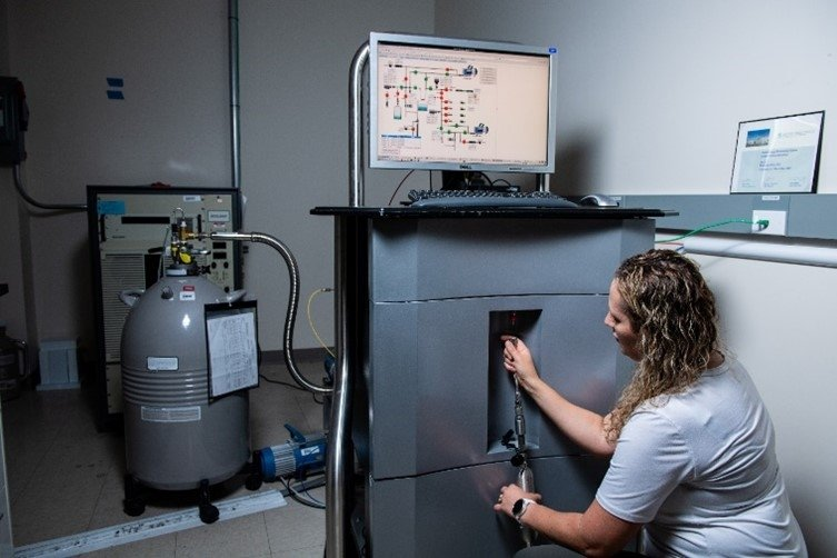 PNNL technician Jennifer Mendez attaches a gas cylinder to one of the systems used to measure samples collected at International Monitoring System stations.