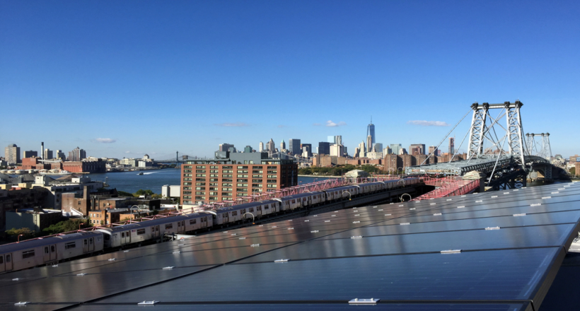 Photo of a solar array overlooking a city with train, bridges, and buildings