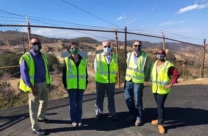 """EM officials gather at the site of the recent demolition of the final DOE-owned buildings at the Energy Technology Engineering Center (ETEC). From left are EM Site Liaison Coordinator John Jones, EM Acting Director of Regulatory, Intergovernmental and Stakeholder Engagement Kristen Ellis, EM Acting Assistant Secretary William """"Ike"""" White, Acting ETEC Federal Project Director Josh Mengers, and Environmental Management Consolidated Business Center Deputy Director Melody Bell."""