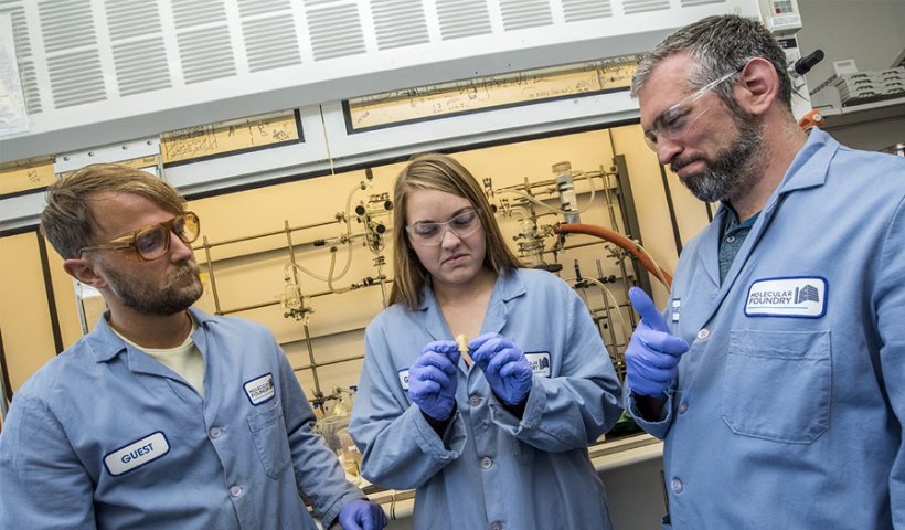 Two men and a woman in blue lab coats and gloves in front of a chemistry laboratory hood.