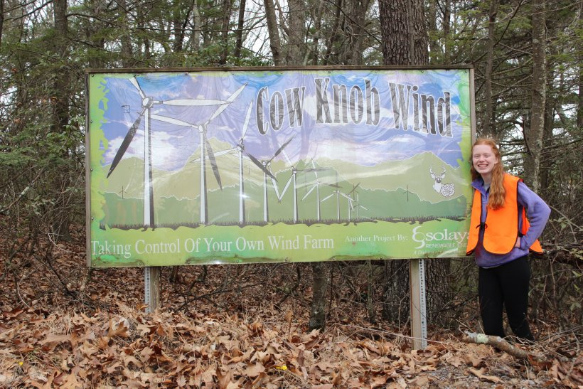 Graduate Jamie Mears stands next to a sign in the woods.