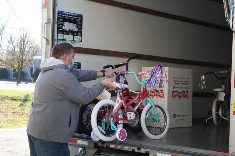 Four Rivers Nuclear Partnership and USW Local 550's Nick Suiter loads one of many bicycles donated for Paducah Toys for Tots.