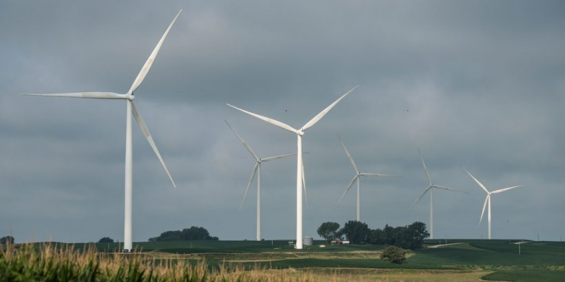 Land-based wind turbines against a cloudy sky.
