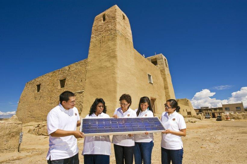 Group holding solar panel in desert