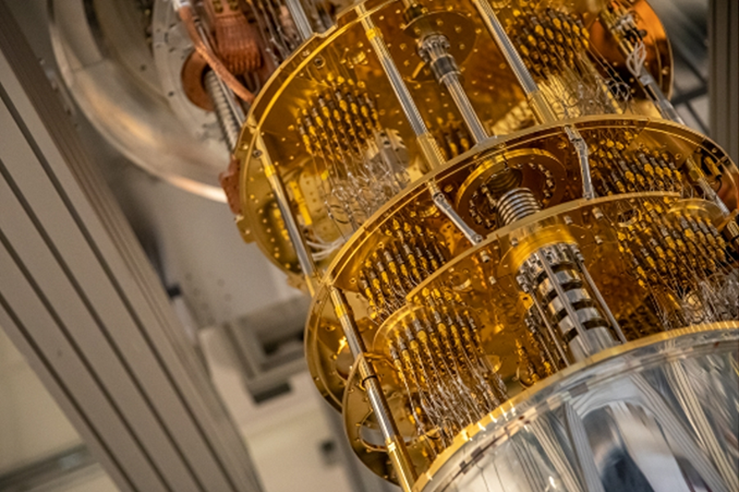 Photograph of part of a quantum computer consisting of gold plates connected by gold wires and silver tubes.
