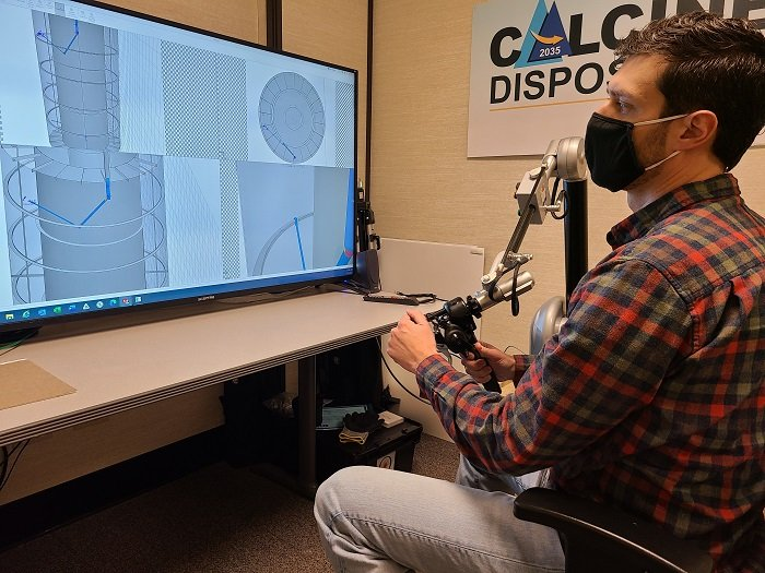 Idaho National Laboratory Site Calcine Retrieval Project Design Engineer Derek Allen tests a robotic arm and related software that uses haptic feedback in advance of full-scale testing.