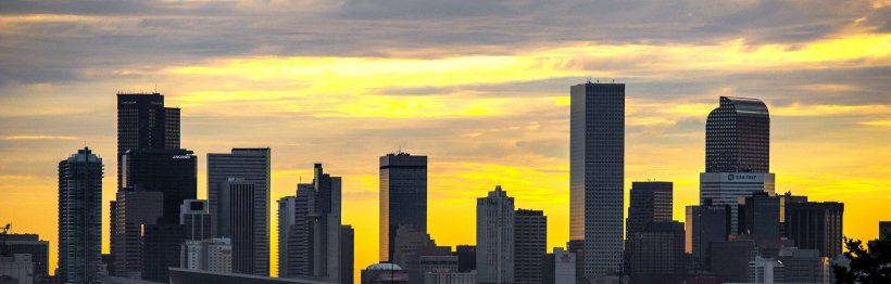 Photo of a city skyline with a multicolored sky beyond.