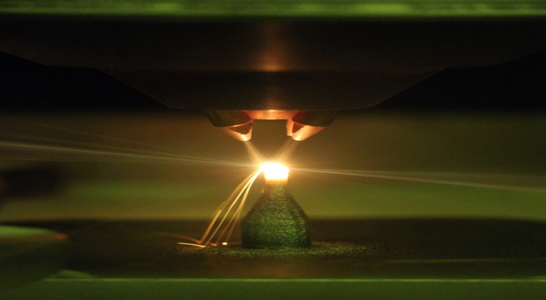 Photograph of a piece of equipment blasting something onto a material that is glowing extremely bright