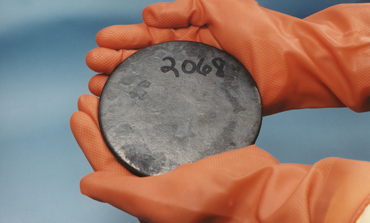 Photo of two gloved hands holding a disc with the number 2068 on it.