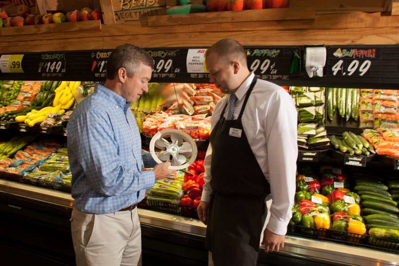 Photo of two men in a supermarket talking.