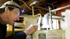 A man examining a hot water heater.