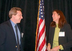 Photo of a man on the left and a woman on the right, standing, facing each other, smiling/laughing, with the American flag between them slightly in the background.