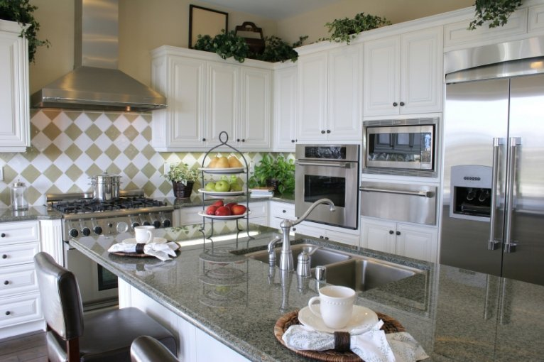 Photo of a modern kitchen, with appliances in the background and a counter / island in the foreground.