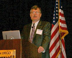 Photo of a man in a suit standing behind a podium, with the American flag on the right.
