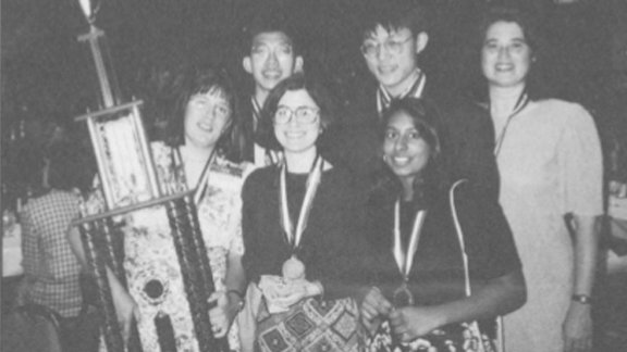 Left to right, in the back: Si Hwang Chin, Peter Chan, Renee Landrum. Front row: coach Penny Sconzo, Susan Born, and Shireen Haque with their 1994 National Science Bowl® trophy.