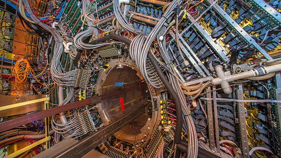 Detectors at the Relativistic Heavy Ion Collider (RHIC) track protons, neutrons, and other subatomic particles produced by ion collisions to better understand quark-gluon plasma.
