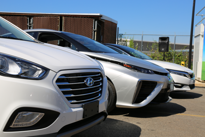 Three white and silver fuel cell vehicles parked next to one another with only the front of the vehicles showing.