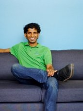 Photo of a young man sitting on a couch, looking at the camera, dressed in jeans and polo shirt.