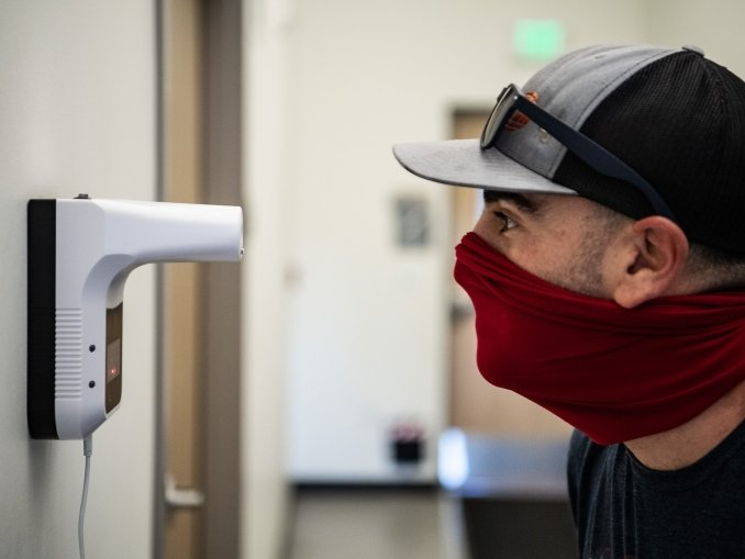 At National Renewable Energy Laboratory , facilities technician scans his temperature at one of the automated temperature stations inside the Research Support Facility (RSF).     Staff on-site are strongly recommended to self-monitor for symptoms by recording twice-daily temperatures as part of the Covid-19 Return to Campus plan.