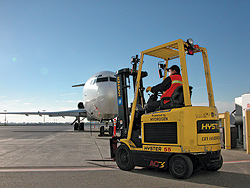 Photo of a Hydrogenics hydrogen-powered forklift in front of an airplane.