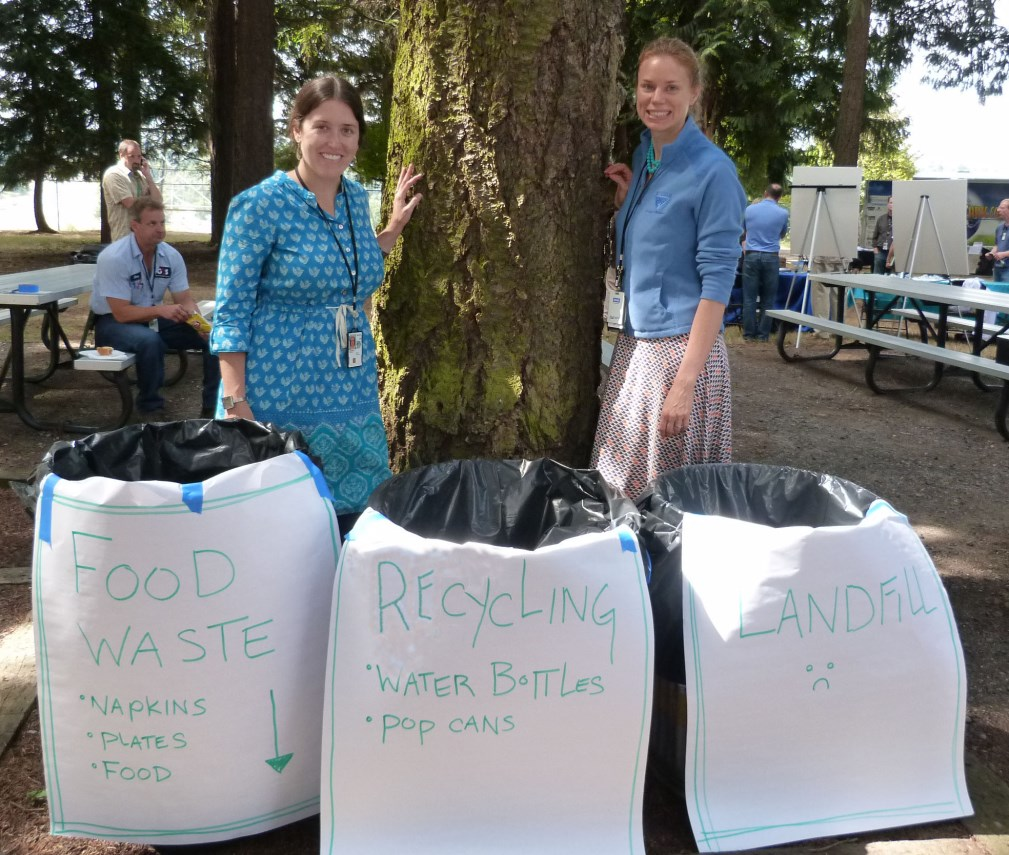 Photo of two women standing in front of a tree with three bins in front of them that read: food waste, recycling, and landfill.