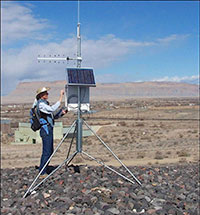 Photo of a man in a hat adjusting controls on a ground antennae with solar panels on it.