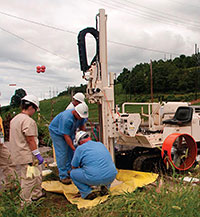 Image of four construction workers working on large piece of equipment.